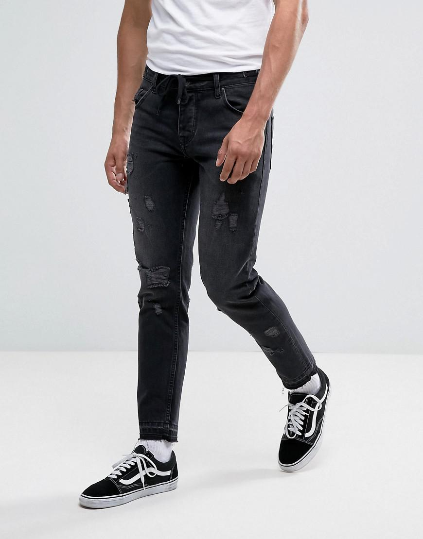 asos slim ankle grazer jeans in washed black with distressing and drawcord
